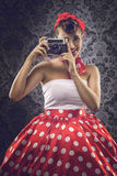 Vintage style - Woman using an old camera in polka dots clothes Stock Images