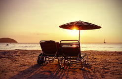 Vintage stylized beach chairs and umbrella at sunset. Stock Photography