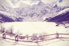 Vintage stylized frozen lake Morskie Oko in Tatra Mountains. Stock Image