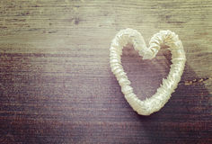 Vintage stylized heart made of shells on wooden background. Stock Images