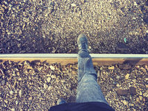 Vintage stylized legs walking on rail track. Stock Photos