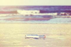 Vintage stylized message in a bottle on beach, shallow depth of Stock Photos