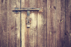 Vintage stylized old metal hasp on wooden door. Royalty Free Stock Photo