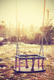 Vintage stylized an old neglected empty swing. Stock Photography