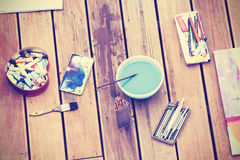 Vintage stylized painting tools on wooden floor Royalty Free Stock Photos