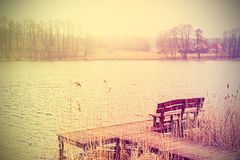Vintage stylized photo of bench at the lake. Royalty Free Stock Photo