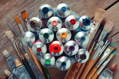 Vintage stylized photo of oil multicolor paint tubes closeup. And artist paintbrushes on wooden desk. Top view Royalty Free Stock Photo