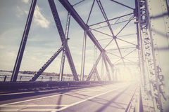 Vintage stylized photo of a steel bridge with sun light. Stock Photo