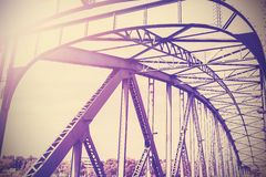 Vintage stylized photo of a steel bridge with sun light. Royalty Free Stock Photography