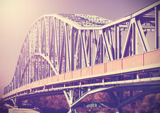 Vintage stylized photo of a steel bridge with sun light Royalty Free Stock Photography