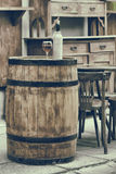 Vintage stylized photo of wooden barrel with bottles of wine. And glass, chair and table in outdoor cafe royalty free stock photos