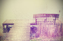 Vintage stylized photo of a wooden bench at the lake. Stock Photography