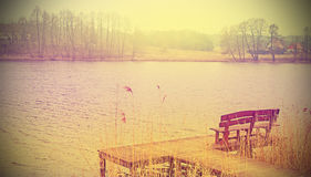 Vintage stylized photo of a wooden bench at the lake. Royalty Free Stock Images