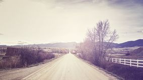 Vintage stylized picture of a countryside road at sunset. Royalty Free Stock Images