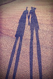 Vintage stylized picture of couple's shadow on beach Royalty Free Stock Image