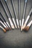 Vintage stylized row of old paintbrushes on rough stone backgrou Royalty Free Stock Image
