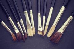 Vintage stylized row of old paintbrushes on rough stone backgrou Royalty Free Stock Photography