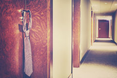 Vintage stylized tie hanging on a hotel closed door handle Royalty Free Stock Photography