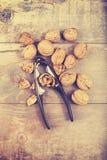 Vintage stylized walnuts and nutcracker on wooden background. Royalty Free Stock Photo