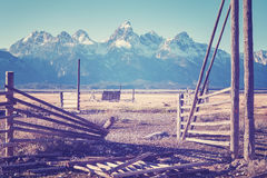 Vintage stylized wooden gate with mountain view. Stock Photos