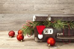 Vintage suitcase with Christmas decorations and santa hat on woo Royalty Free Stock Photo
