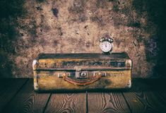 Vintage suitcase and a clock on wooden floor. Processing in vintage style. The concept of travel Stock Images