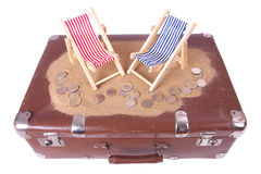 Vintage suitcase with euro coins lie in front of toy beach chair Royalty Free Stock Photos