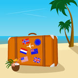 Vintage suitcase with flag stickers placed on tropical beach with peaceful sea. And palm trees Royalty Free Stock Photo