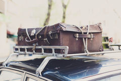 Vintage suitcase on an old car roof rack. Stock Images