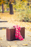 Vintage suitcase with pink scarf on alley Royalty Free Stock Photo