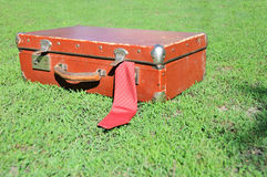 Vintage suitcase. Red old suitcase on background of green grass Royalty Free Stock Photography