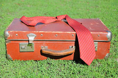 Vintage suitcase. Red old suitcase on background of green grass Stock Photos
