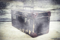 Vintage suitcase with smoke  on wooden table. Selective focus Royalty Free Stock Photography