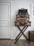 Vintage suitcases. Beautifully stacked suitcases in front of a white wallpaper and a closed door Stock Photo