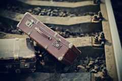 Vintage suitcases are forgotten on railway rails. Royalty Free Stock Photo