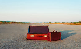 Vintage suitcases. Vintage open suitcase and small bag on road, space for text in upper part of image. Travel theme Royalty Free Stock Photos