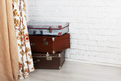 Vintage suitcases pile indoors, travel concept. Old vintage suitcases pile. Vintage old suitcases near the white brick wall behind the beige curtain. Interior Royalty Free Stock Photography