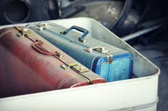 Vintage Suitcases. Vintage pink and blue suitcases in a white bucket Royalty Free Stock Photo
