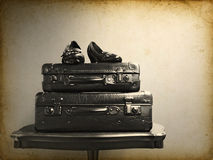 Vintage suitcases and shoes on a table Royalty Free Stock Photo