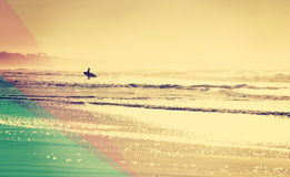Vintage summer beach with surfer in the water