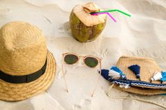 Straw hat, coconut and sun glasses on a tropical beach. royalty free stock images