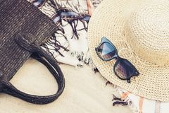 Vintage summer wicker straw beach bag, sun glasses, hat cover-up beachwear wrap on the sand, tropical background royalty free stock images