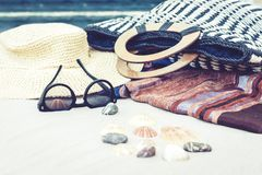 Vintage summer wicker straw beach bag, sun glasses, hat, cover-up beachwear wrap on the sand, tropical background stock images