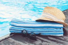 Vintage summer wicker straw beach hat, sun glasses, blue towel near swimming pool, tropical background royalty free stock images