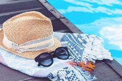 Vintage summer wicker straw beach hat, sun glasses, cover-up beachwear wrap near swimming pool, tropical background royalty free stock photos