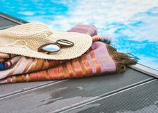 Vintage summer wicker straw beach hat, sun glasses, cover-up beachwear wrap near swimming pool, tropical background stock photos