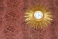 Vintage Sun Rays Clock. Clock with golden rays around the clock on the fabric wall royalty free stock image