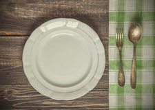 Vintage table appointments. Vintage toned picture of the ancient fork and spoon lying at the old table near the dish Royalty Free Stock Image