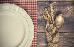 Vintage table appointments. Vintage toned picture of the fork and spoon with the ears of wheat lying at the old table near the dish Stock Photos