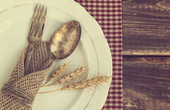 Vintage table appointments. Vintage toned picture of the fork and spoon with the ears of wheat on the old dish at wooden background. Top view Stock Photo